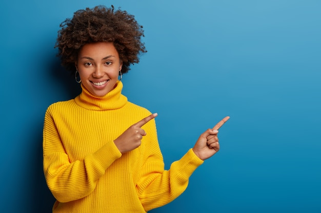 Cheerful young woman in yellow sweater points aside at copy space, shows cool advertisement against blue background