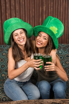 Cheerful young women hugging and clanging glasses of drink on settee