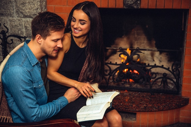 Cheerful young women sit on man's lap and look at him. she smiles and hold book opened. guy look at it. model turning page. they sit at fireplace.