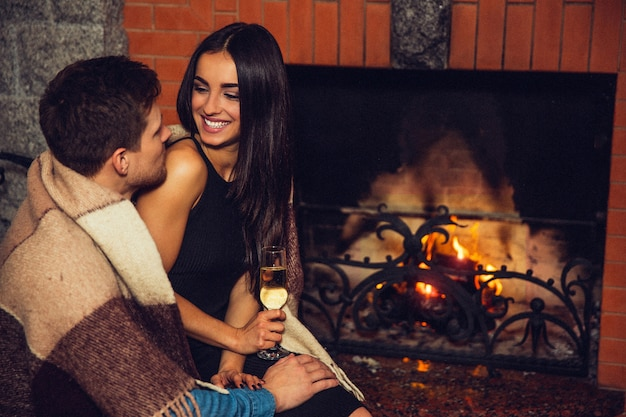 Cheerful young women sit on man's lap and look at him. she smiles. model hold glass of alcohol. they sit in room at fireplace. guy's shoulders cover with blanket.