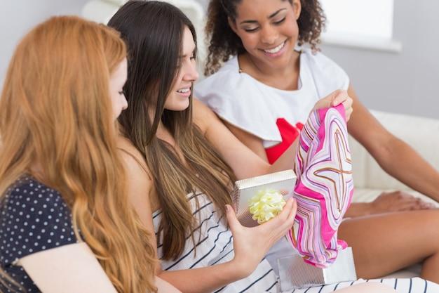 幸せな若い女性の驚くべき友人と贈り物