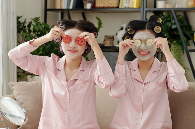 Веселые молодые женщины с увлажняющими масками на лицах прикрывают глаза ломтиками помидора и огурца