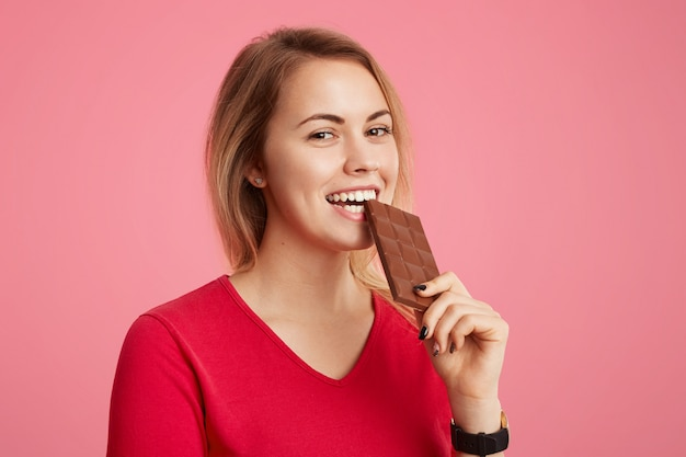 Cheerful young young woman enjoys sweet chocolate, doesn`t think about figure, being in good mood as eats sweets, poses against pink. people, desserts, sweet tooth