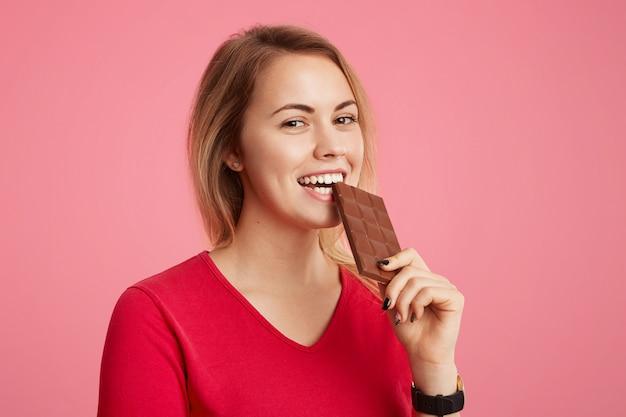 Веселая молодая девушка наслаждается сладким шоколадом, не думает о фигуре, находится в хорошем настроении, ест сладости, позирует на фоне розового. люди, десерты, сладкоежки