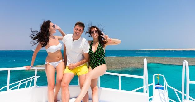 화창한 여름날 요트에 서서 웃고 있는 쾌활한 젊은이들, 머리카락이 자라는 바람, 배경의 아름다운 바다
