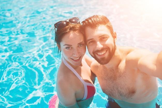 屋外のプールで休んでいる陽気な若々しい男と女。水中のカップル。男たちは夏の自分撮りをします。