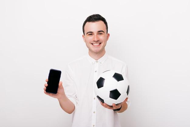 Веселый юнг мужчина смотрит на камеру и держит телефон и футбольный мяч