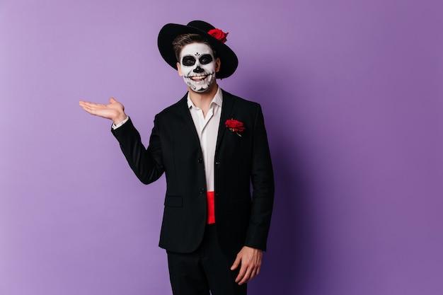 笑顔でスタジオに立っている陽気なゾンビ少年。紫色の背景で隔離のムエルテメイクで面白いヨーロッパ人の屋内写真。
