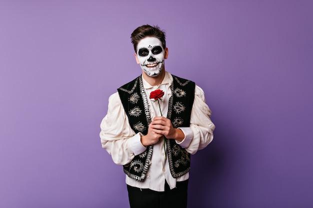 花でポーズをとる白いシャツの陽気なゾンビ男。赤いバラと明るい白人男性の屋内写真。