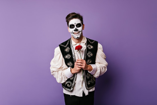 Cheerful zombie man in white shirt posing with flower. indoor photo of blithesome caucasian guy with red rose.