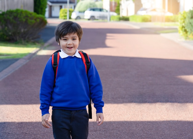 Портрет счастливого мальчика ребенка носит рюкзак идя на дорогу в утре, ребенк школы cheerfull с усмехаясь стороной и возбужденный назад к shool, концепции образования.