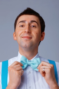 Жизнерадостный молодой человек поправляет голубой галстук-бабочку.