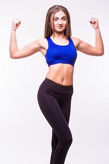 Весело улыбающаяся спортивная женщина смешанной расы демонстрирует бицепс, изолированные на белом фоне