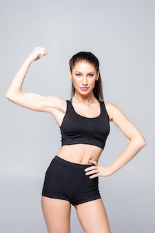 Cheerfully smiling sporty woman demonstrating biceps, isolated