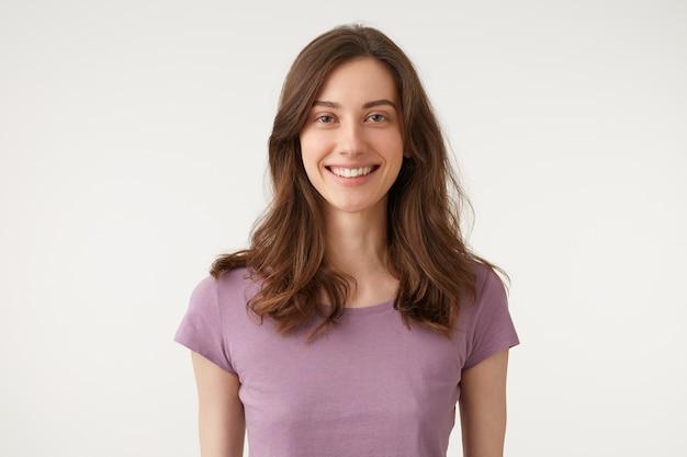 보라색 티셔츠를 입고 직접 카메라를보고 유쾌하게 널리 웃는 예쁜 여자