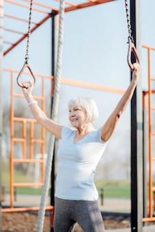 陽気さ。野外で運動しながらチンアップをしているうれしいブロンドの女性