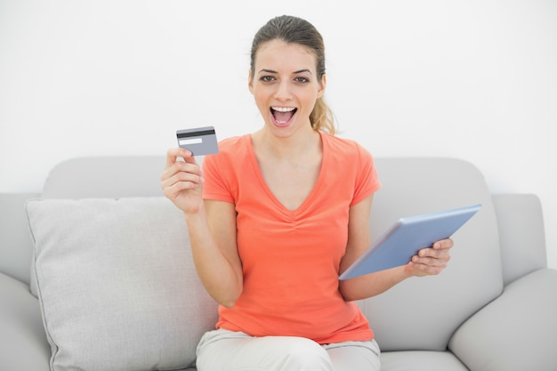 Cheering brunette woman showing her credit card holding her tablet