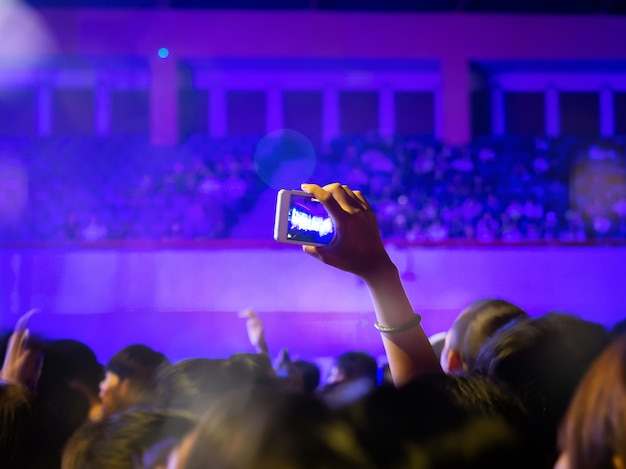 Cheering fans take a photograph or video with smartphone in a free live concert