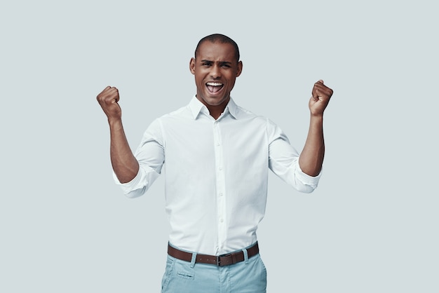 Cheering. handsome young african man gesturing and smiling while standing against grey background