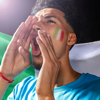 Cheering man with the italian flag on his face