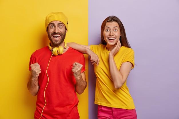 Esultante coppia millenaria in posa contro la doppia parete colorata