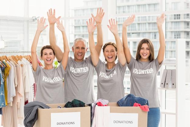 Cheering volunteers holding arms up