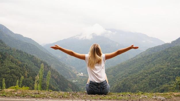 山の頂上の自然とライフスタイルで女性ハイカーが両手を広げて応援する