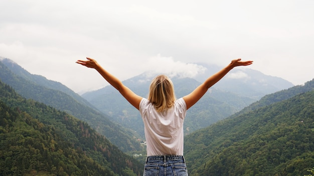 山の頂上で女性ハイカーが両手を広げて応援する