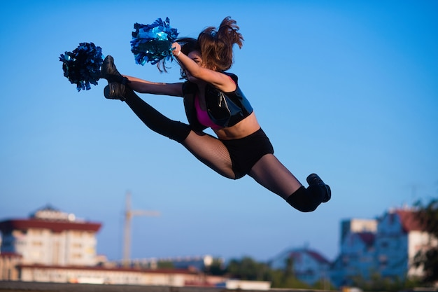 Cheerleader girl with pompoms performs acrobatic element outdoors on the roof