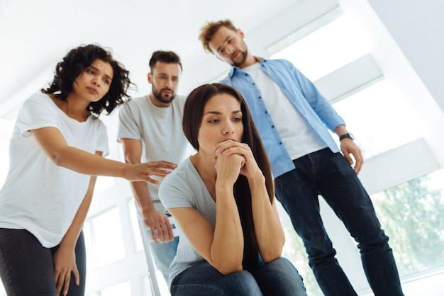 陽気で美しいストレスのたまった女性は、自分の問題について考え、友達に囲まれながら落ち込んでいると感じています