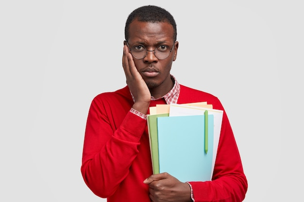 Cheerless black man has dejected facial expression, keeps hand on cheek, feels tired of studying, holds textbooks with pen, going to library