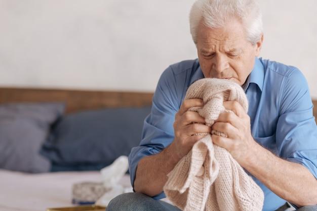 Безрадостный подавленный пожилой мужчина держит вязаную куртку своей умершей жены и вспоминает о ней, находясь в горе