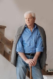 Безрадостный подавленный пожилой мужчина, опираясь на трость и чувствуя себя несчастным, стоя посреди комнаты