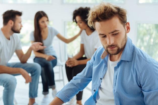 彼の問題について考え、非常にストレスを感じながら不幸を感じている元気のないハンサムな若い男