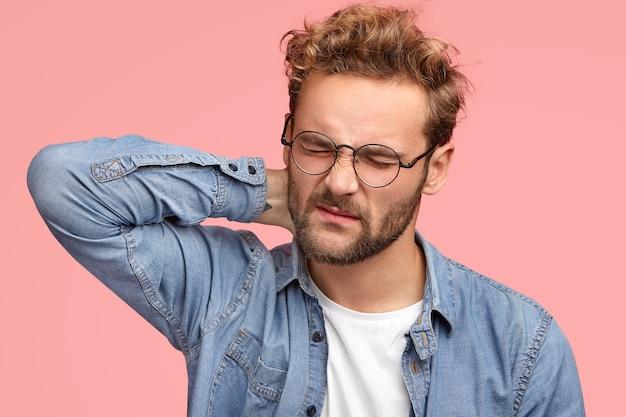 쾌활한 남자는 목이 뻣뻣 해지고 앉아있는 생활 방식으로 고통을 겪으며 컴퓨터에서 오랫동안 일하고 불만족스럽게 얼굴을 찌푸리고 안경과 데님 셔츠를 입고 실내에 서 있습니다.