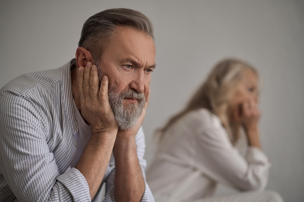 彼の妻から離れて座っている元気のない静かな男