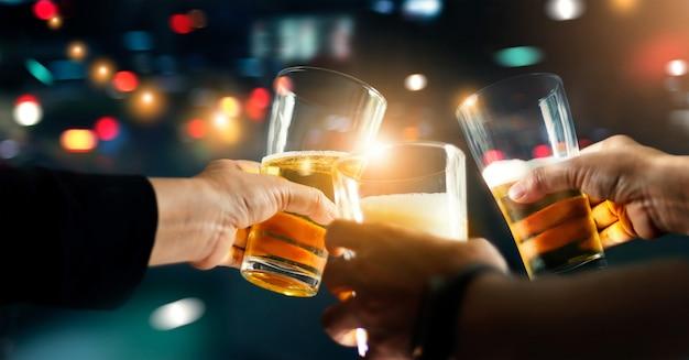 Приветствия, звенящие друзьями с пивным напитком в вечеринке ночью после работы