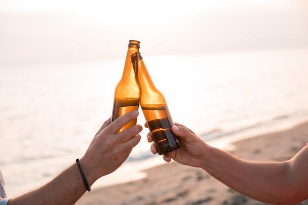乾杯!ビーチでビールのボトルで乾杯の手のクローズアップ。お祝いのコンセプト