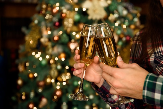 Cheers!close up photo of two people holding glasses of shampagne on xmas.