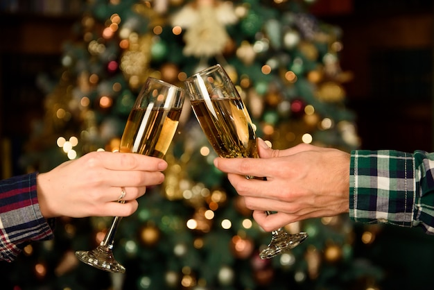 Cheers. close up photo of two people holding glasses of shampagne on xmas.