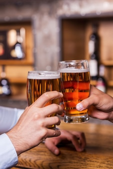 Cheers! close-up of two men toasting with beer at the bar counter