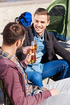 Cheers to friendship! top view of two handsome young men cheering with beer and smiling while sitting near the tent and on the sand