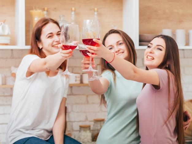 乾杯。女の子のキッチンパーティーとお祝い。赤ワインとグラスをチリンと鳴らす若い女性