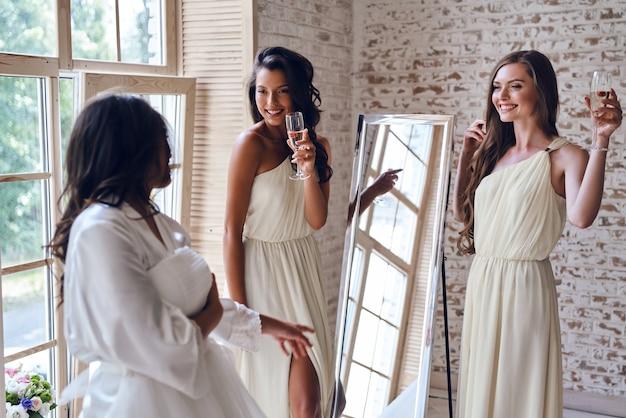 건배 소녀들! 피팅룸에서 신부에게 미소를 지으며 안경을 들고 있는 두 명의 매력적인 젊은 여성