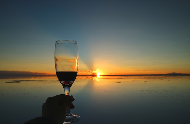Cheers to the gorgeous sunset on the mirror effect of uyuni salt flats, bolivia, south america