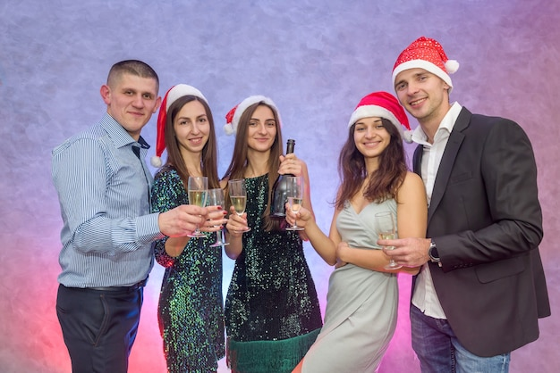 Cheers! group of friends celebrate and raise glasses of champagne for toast, 2020 new year