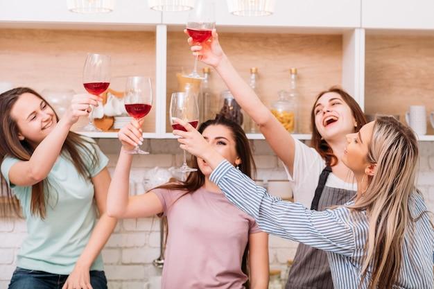 乾杯。ホームパーティーをしている友達のグループ。週末のレジャー。アーバンライフスタイル。赤ワイングラスをチリンと鳴らす若い女性。
