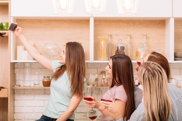 乾杯。ホームパーティーをしている友達のグループ。週末のレジャー。アーバンライフスタイル。自撮りをしている若い女性。