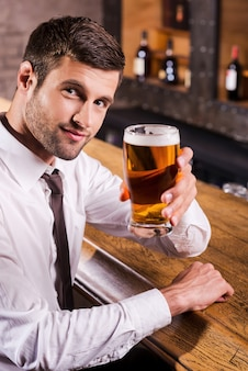 Cheers! handsome young man in shirt and tie toasting with beer and looking at camera while sitting at the bar counter