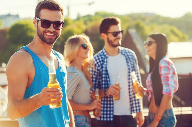 Ваше здоровье!! счастливый молодой человек держит бутылку пива и смотрит в камеру, пока трое людей веселятся на заднем плане